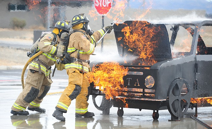 Jace Hall handles the nozzle and Russell Smith opens the hood as new Central Arizona Fire and Medical Authority firefighters do their final academy drill in front of friends and family Feb. 22, 2017, in Prescott Valley. (Les Stukenberg/Courier, File)