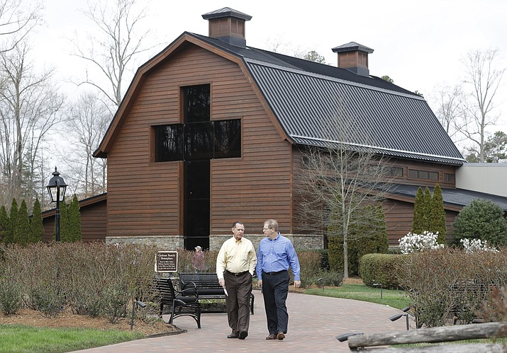 Visitors leave the Billy Graham Library in Charlotte, N.C., Wednesday, Feb. 21, 2018. Graham, who transformed American religious life through his preaching and activism, becoming a counselor to presidents and the most widely heard Christian evangelist in history, has died. Spokesman Mark DeMoss says Graham, who long suffered from cancer, pneumonia and other ailments, died at his home in North Carolina on Wednesday, Feb. 21, 2018. He was 99. (AP Photo/Chuck Burton)