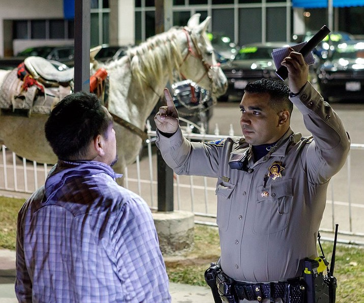 In this photo released by the California Highway Patrol, an unidentified officer administers a field sobriety test to a rider who made his way onto State Route 91 and was arrested for riding a horse under the influence.