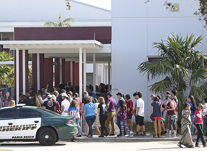 Parents and students walk into Marjory Stoneman Douglas High School on Sunday, Feb. 25, 2018, for an open house as parents and students returned to the school for the first time since 17 people were killed in a mass shooting at the school in Parkland, Fla. on Feb. 14.