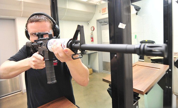 Cody Cates, of Insight Firearms, demonstrates a shooting technique with a Bushmaster XM-15 which is a variant of the AR-15 style sporting rifle Tuesday afternoon.