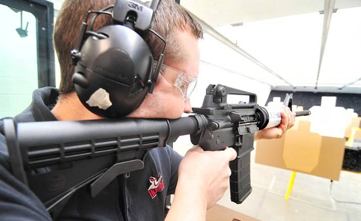 Cody Cates, of Insight Firearms, shoots a Bushmaster XM-15 -- a variant of the AR-15 style sporting rifle -- Tuesday afternoon. (Les Stukenberg/Courier)