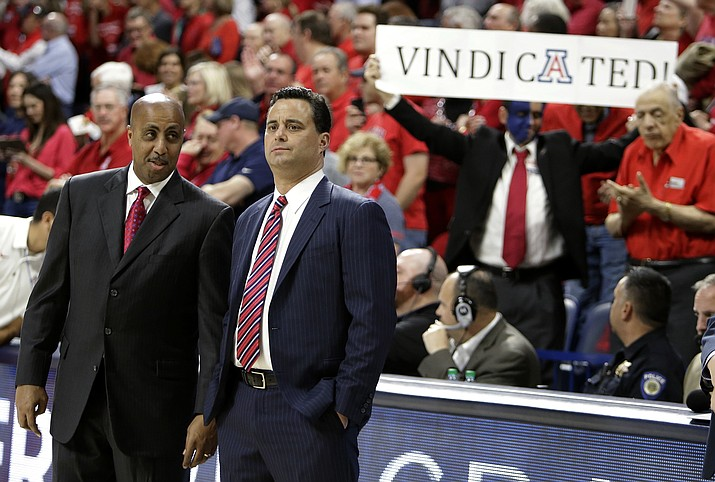 Arizona associate head coach Lorenzo Romar, left, and coach Sean Miller talk before the team's NCAA college basketball game against Stanford, Thursday, March 1, 2018, in Tucson.