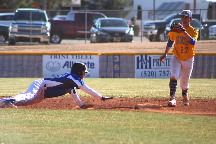 Kingman Academy's Peter High slides back to second base as Kingman's David Lopez awaits the throw. The Tigers used a seven-run third inning to defeat the Bulldogs, 7-2.