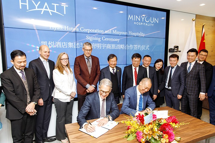 Seated at left, Mark Hoplamazian, president and chief executive officer of Hyatt Hotels Corporation, signs a strategic development agreement with Zhang Jianming, chairman of Tianfu Minyoun Hospitality, who is seated at right. The agreement is intended to expand Hyatt Place and Hyatt House hotels throughout China. The two men are pictured with members of Hyatt Hotels Corporation, Tianfu Minyoun Hospitality, Road King Infrastructure Ltd., Sichuan Tianfu Bank, and Nuo Ruide. (John Gress Photography/Courtesy)