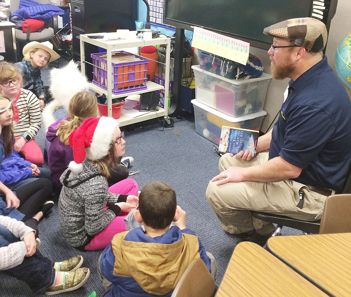 "Prescott Unified School District Superintendent Joe Howard reads ""The Young Man and the Sea,"" a story that appeals to him as a hobby fisherman who early in his life worked as a crab fisherman in Alaska. (Nanci Hutson/Courier)"