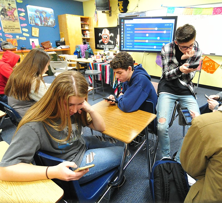 Sophia DeVito, Geneva Raber, Jet Burginger and Cade Tutrone in Spanish 2 class use their cell phones to answer a group quiz at Prescott High School Thursday morning. (Les Stukenberg/Courier)