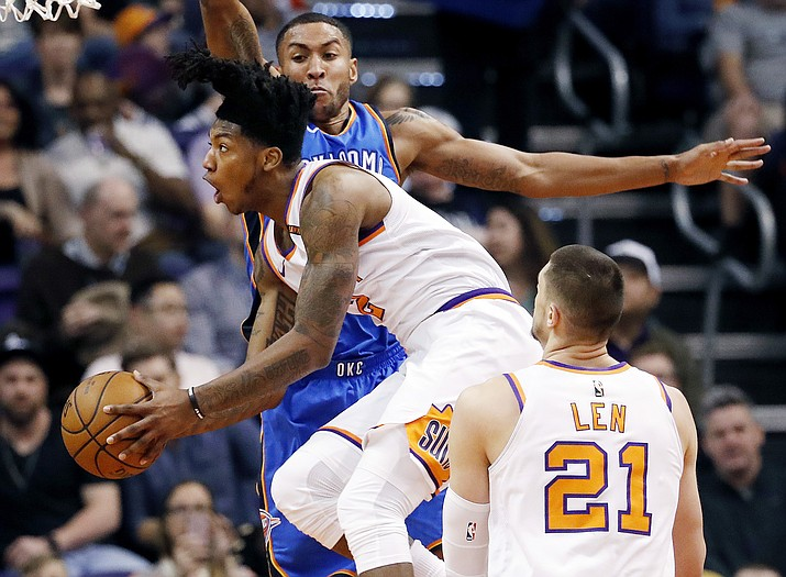 Phoenix Suns guard Elfrid Payton drives to the basket as Oklahoma City Thunder guard Josh Huestis defends and Phoenix Suns center Alex Len (21) looks on during the first half of an NBA basketball game Friday, March 2, 2018, in Phoenix.