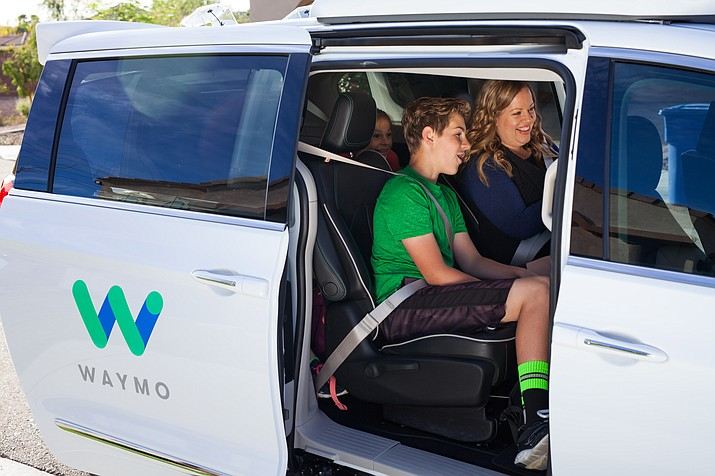 Waymo early riders Trey, Candace and Izzy in the Chrysler Pacifica Hybrid minivan picking them up. (Waymo.com/Courtesy)