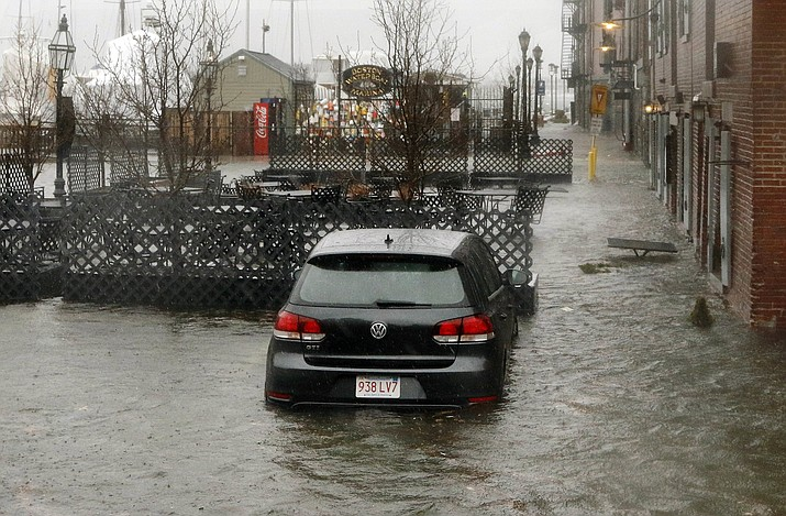 A car sits in a Long Wharf parking lot flooded by water from Boston Harbor at high tide during a major nor'easter that pounded the East Coast, Friday, March 2, 2018, in Boston. (AP Photo/Bill Sikes)