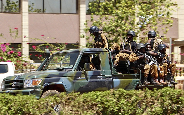 Troops ride in a vehicle near the French Embassy in central Ouagadougou, Burkina Faso, Friday March 2, 2018. Gunfire and explosions rocked Burkina Faso's capital early Friday in what the police said was a suspected attack by Islamic extremists. By midday the gunfire became intermittent and helicopters flew above the French Embassy in Ouagadougou.(AP Photo/ Ludivine Laniepce)