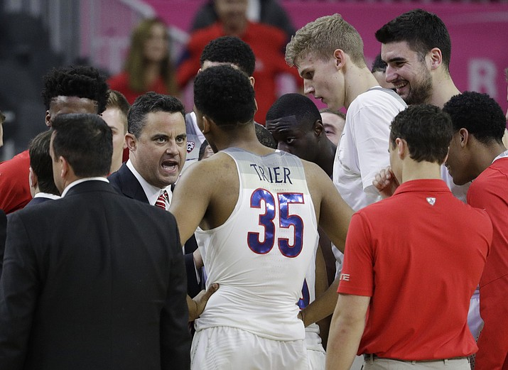 Arizona coach Sean Miller speaks with his players. After days of limbo, on Thursday the UA announced Miller would remain as coach of the Wildcats and he led them to a win that night against Stanford. (AP Photo/John Locher)