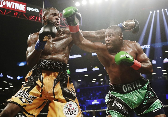 Deontay Wilder, left, and Luis Ortiz trade punches during the third round of the WBC heavyweight championship bout Saturday, March 3, 2018, in New York. Wilder stopped Ortiz in the 10th round.