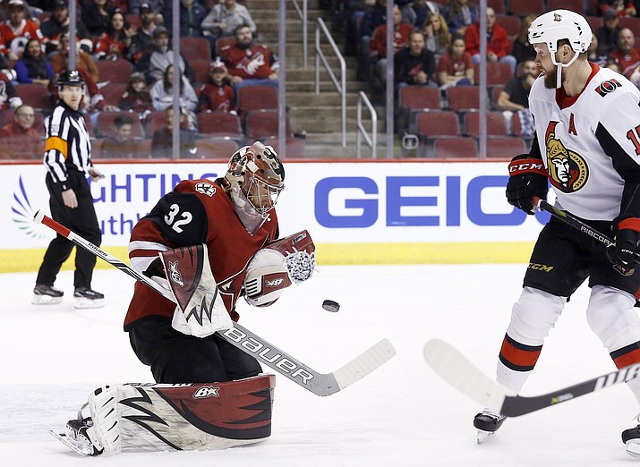 Arizona Coyotes goaltender Antti Raanta (32) makes a save on a shot as Ottawa Senators left wing Zack Smith, right, looks on during the first period of an NHL hockey game Saturday, March 3, 2018, in Glendale.