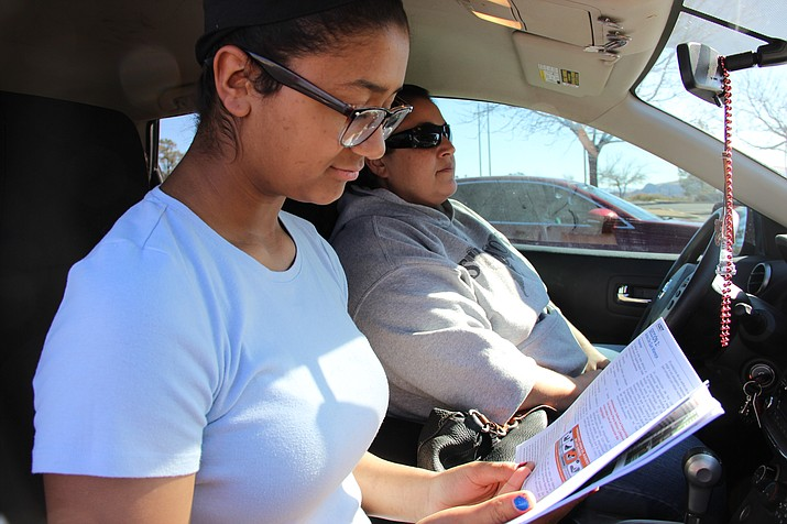Audrey Gunn, at left, reviews an Arizona Driver License Manual outside the Motor Vehicle Department in Prescott after failing the test there, on her first attempt. Audrey's mother, Rachel (in the driver's seat), pulled Audrey out of school Thursday, March 1, so Audrey could take the test in person at the MVD office. On Monday, March 5, Arizona began allowing the driving learner's permit test to be taken online. (Photo by Max Efrein/Courier)
