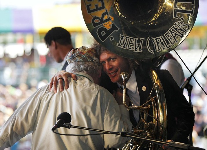 In this May 6, 2012, file photo, Ben Jaffe, tuba player and director of the Preservation Hall Jazz Band hugs George Wein, founder of the New Orleans Jazz and Heritage Festival, as well as the Newport Jazz Festival, after Wein performed a song on the piano at the New Orleans Jazz and Heritage Festival in New Orleans. Someone has stolen Preservation Hall's signature sousaphone, and there's a reward offered for its return. Jaffe posted a message about the theft on the jazz venue's Facebook page, saying it was stolen after a performance Saturday, Feb. 24, 2018. (AP Photo/Gerald Herbert, File)