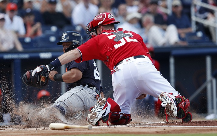 Detroit Tigers' Miguel Cabrera (24) is tagged out by Washington Nationals catcher Matt Wieters (32) as he tries to score on a Jim Adduci base hit in the first inning of a spring training baseball game, Sunday, March 4, 2018, in West Palm Beach, Fla. (John Bazemore/ap)
