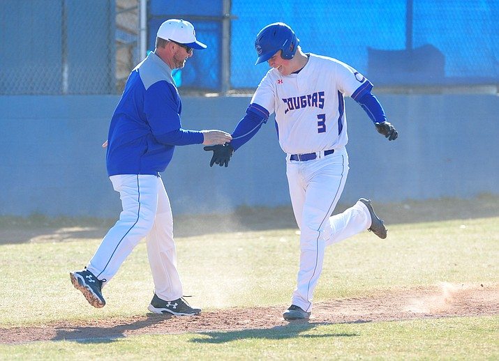 Chino Valley's Ben Grandy (3) shakes hands with head coach Mark Middleton as he rounds third base after his first inning grand slam as the Cougars took on Camp Verde on Monday, March 5, 2018, in Chino Valley. The Cougars won 20-8. (Les Stukenberg/Courier)