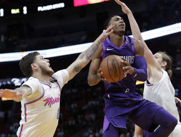 Phoenix Suns' Shaquille Harrison, center, drives as Miami Heat's Tyler Johnson (8) and Kelly Olynyk, defend during the first half Monday, March 5, 2018, in Miami. Harrison is a former Northern Arizona Suns guard under his second 10-day contract with the big club. (Lynne Sladky/AP)