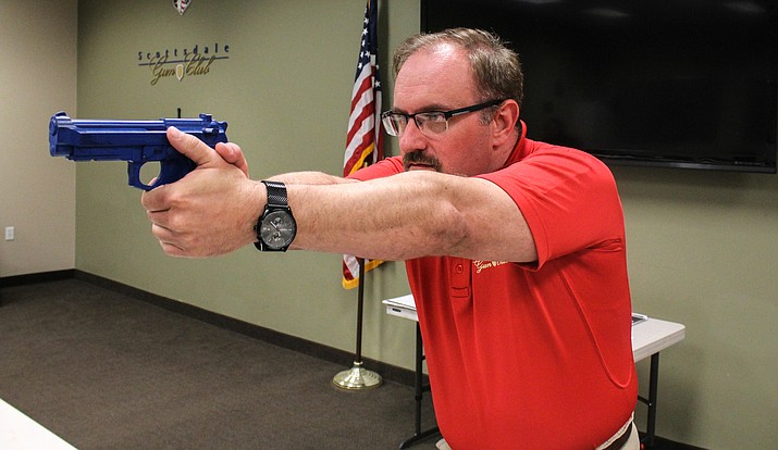 Firearms instructor Ryan Arnold, using a blue plastic gun, at a class teaching children and families how to safely handle weapons. (Photo by Melina Zuniga/Cronkite News)