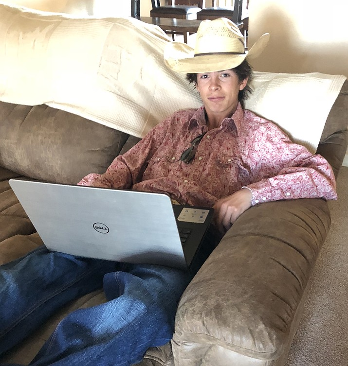 John Duey, 15, on the couch with his laptop as he does homework in his spare time. (Courtesy photo by Ruby Duey)