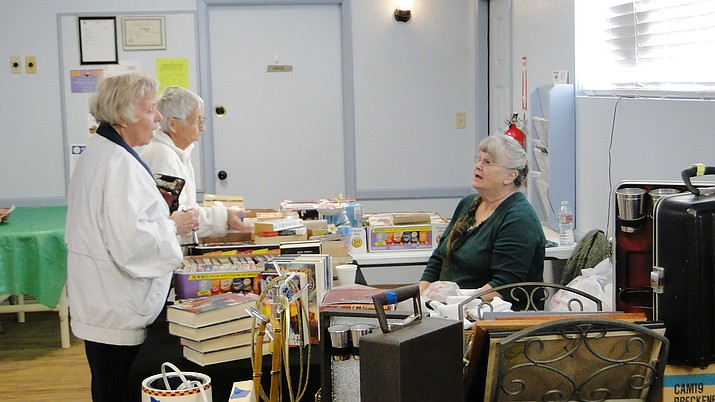 Mo Emmett of the library talks with Community Yard Sale patrons at her table. 