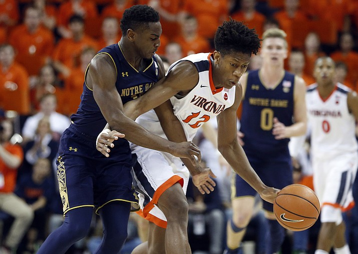 Virginia guard De'Andre Hunter (12) is fouled by Notre Dame forward Juwan Durham (11) during the second half of an NCAA college basketball game in Charlottesville, Va., Saturday, March 3, 2018. Virginia won the game 62-57. (Steve Helber/AP, File)