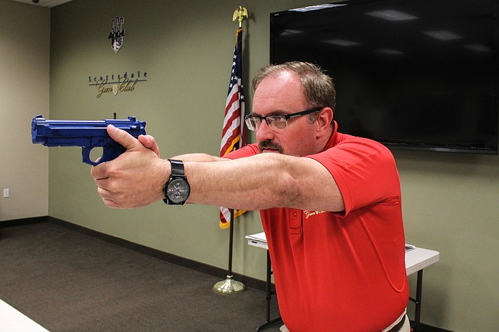 Firearms nstructor Ryan Arnold, using a plastic blue gun,  at a class teaching children and families how to safely handle weapons. (Photo by Melina Zuniga/Cronkite News)