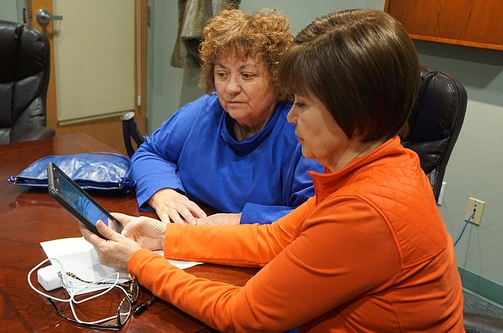 Prescott resident Vera Dicicco, left, listens as Prescott Public Library volunteer Paula Williams describes the features of an iPad equipped with assistive technology apps for the vision impaired. The tablet is available through a new program at the library -- You Too! Community Access and Engagement through Assistive Technology. (Cindy Barks/Courier)
