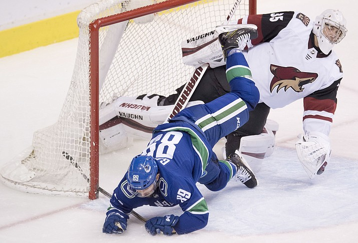 Vancouver Canucks center Sam Gagner (89) flies over Arizona Coyotes goaltender Darcy Kuemper during the third period of an NHL hockey game Wednesday, March 7, 2018, in Vancouver, British Columbia.
