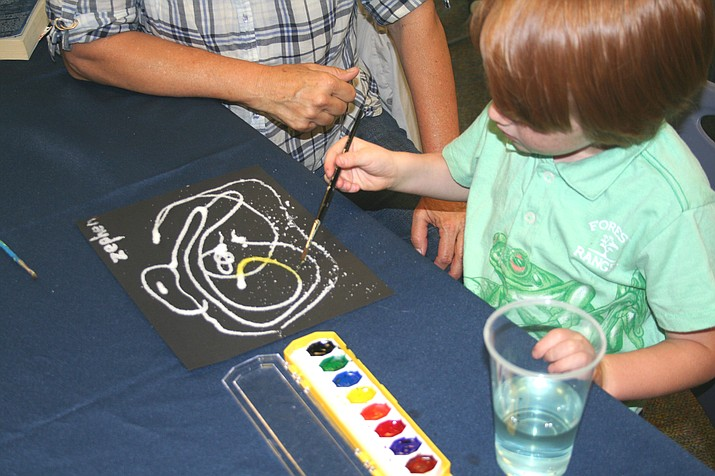 A child and father at the Prescott Public Library painting on Art Day. (Prescott Public Library/Courtesy)