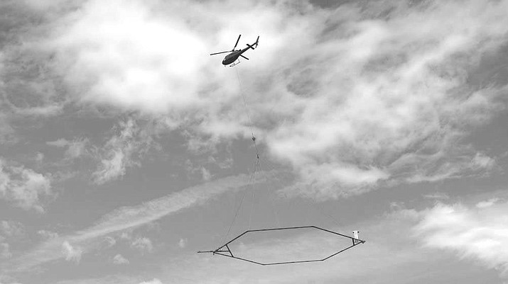 The sensor towed by the helicopter measures tiny electromagnetic signals used to map properties of the earth's subsurface.
