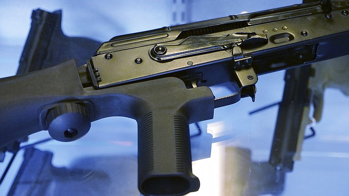 "In this Oct. 4, 2017 file photo, a device called a ""bump stock"" is attached to a semi-automatic rifle at the Gun Vault store and shooting range in South Jordan, Utah. The Trump administration is proposing banning bump stocks, which allow guns to mimic fully automatic fire and were used in last year's Las Vegas massacre. The Justice Department's regulation, announced Saturday, March 10, 2018, would classify the device as a machine gun prohibited under federal law. The move was expected after President Donald Trump ordered officials to work toward a ban after 17 people were killed at a Florida high school. (AP Photo/Rick Bowmer, File)"