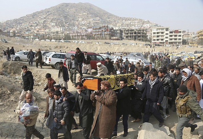 "In this Jan. 28, 2018, file photo, men carry the coffin of a relative who died in the Jan. 27 deadly suicide attack in Kabul, Afghanistan. The deadly explosion caused by a suicide bomber driving an ambulance in the capital. Is Afghanistan really America's forgotten war? Consider this: At a Senate hearing this week on top U.S. security threats, the word ""Afghanistan"" was spoken exactly four times, each during introductory remarks. In the ensuing two hours of questions for intelligence agency witnesses, no senator asked about Afghanistan, suggesting little interest in a 17-year war with nearly 15,000 U.S. troops supporting combat against the Taliban. (AP Photo/Rahmat Gul, File)"