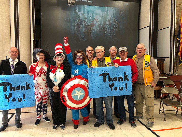 Left to right: Brian Roos (Service Manager, Liberty Kia (donated $600), Ellen Anderson (Title 1 reading instructor), Cat in the Hat (Katie Harrell), Principal Karen Hughes (spent the day as Captain America due to students fulfilling their reading goal), Jim Myers (Prescott Sunrise Lions Vice President), Don White (Prescott Sunrise Lions President), Bill Brye (Lion), Jim Howard (representing Hungry Kids) and Mark Anderson (Lion).