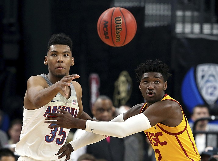 Arizona's Allonzo Trier, left, passes the ball as Southern California's Jonah Mathews defends during the first half of the Pac-12 championship Saturday, March 10, 2018, in Las Vegas. (Isaac Brekken/AP)