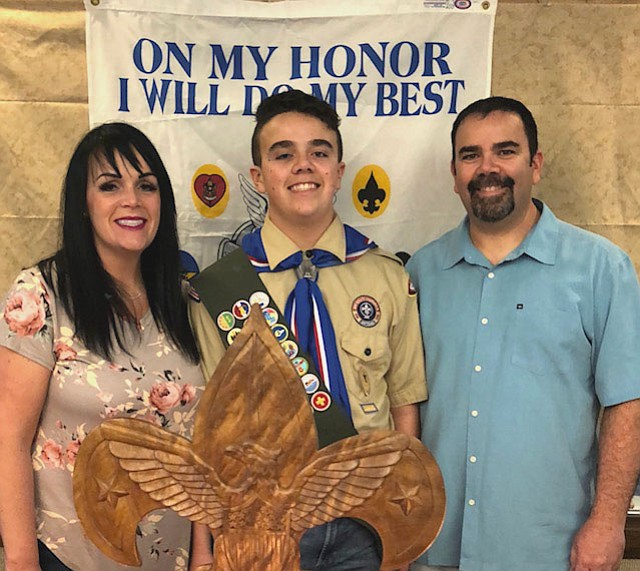 Eagle Scout Kobe Hales poses for a photo with his parents, Mandi (left) and James Hales.