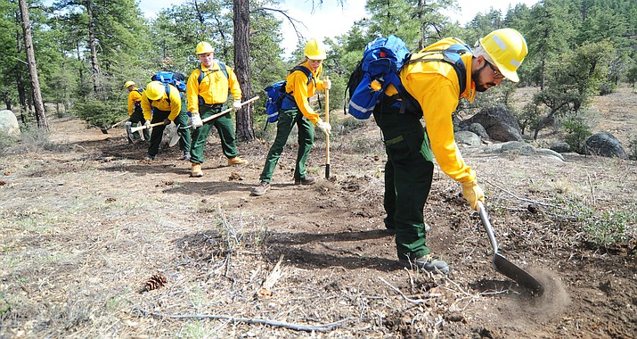 Prescott National Forest employee Francisco Anaya leads a group of basic wildland firefighting students as they cut a line during the Arizona Wildfire Academy field day Wednesday, March 15, in Prescott. (Les Stukenberg/Courier)