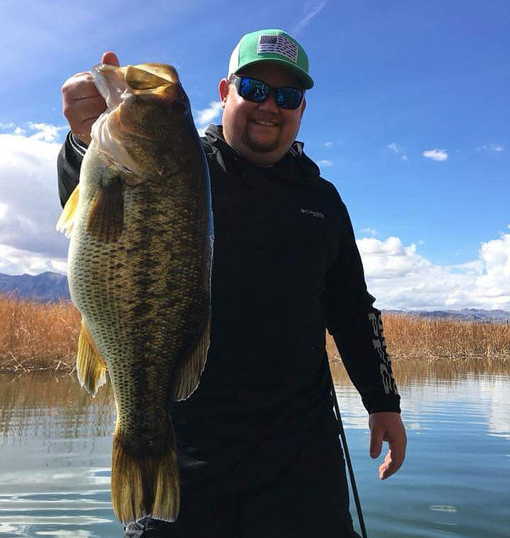 Chris Morris holds the 7 lb. 6 oz. largemouth bass he caught while fishing at Lake Havasu.