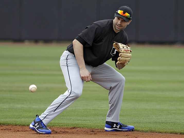 In this Feb. 27, 2018, file photo, Major League Baseball free agent second baseman Neil Walker fields a ground ball during infield drills before a scrimmage game  in Bradenton, Fla. A person familiar with the negotiations says free agent infielder Neil Walker and the New York Yankees are close to an agreement on a one-year contract for about $5 million. (Chris O'Meara/AP, File)