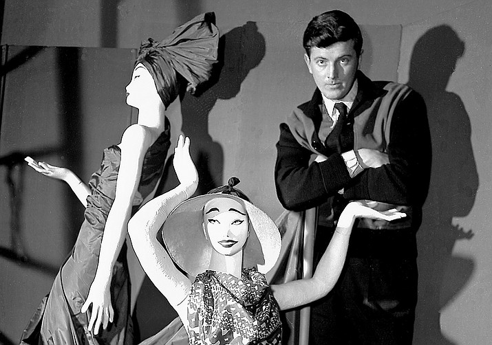 "In this Feb.1 1952 file photo, French fashion designer Hubert de Givenchy poses with mannequins in his shop in Paris. French couturier Hubert de Givenchy, a pioneer of ready-to-wear who designed Audrey Hepburn's little black dress in ""Breakfast at Tiffany's,"" has died at the age of 91. (AP Photo, File)"