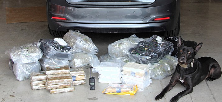 "Yavapai County Sheriff's Office K-9 ""Vader"" sits with nearly $1 million worth of drugs after a deputy made a traffic stop for an equipment violation Monday, March 12, 2018, in Ash Fork. After Vader completed an external sniff of the vehicle and alerted the deputy, 47.5 pounds of cocaine and 27.5 pounds of marijuana were discovered. (YCSO/Courtesy)"