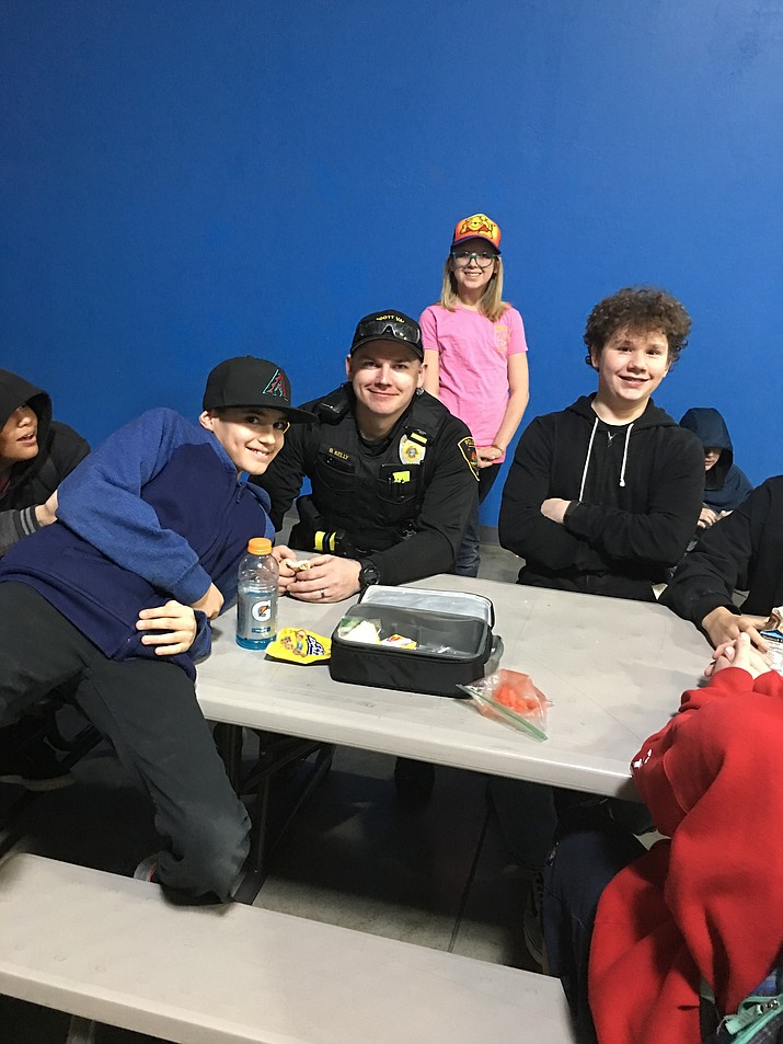 Prescott Valley Police Officer Branden Kelly visits with middle school students during lunch hour on March 2. From left are Joseph Marchesano, Officer Kelly, Laureli Potter and Samuel Snyder. (PVS/Courtesy)