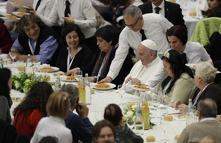 In this Nov. 19, 2017 file photo, Pope Francis is served gnocchetti during a lunch with several hundred poor people, at the Vatican on World Day of the Poor. When Cardinal Mario Jorge Bergoglio appeared five years ago, on March 13, 2013, at the main window of St. Peter's Loggia in a white cassock and without solemnity greeted the chanting crowd in the square with a casual 'buonasera' (good evening) it was immediately apparent that Pope Francis's style would be different, folksier than that of other popes. (AP Photo/Andrew Medichini, files)
