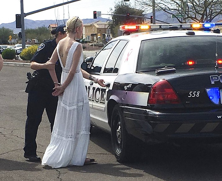 Pictured is 32-year-old Amber Young during her arrest on suspicion of impaired driving, Monday, March 12, 2018, in southern Arizona. Police say Young became involved in a car crash in Marana as she was driving to her wedding. One person suffered minor injuries in the three-vehicle crash. (Marana Police Department)