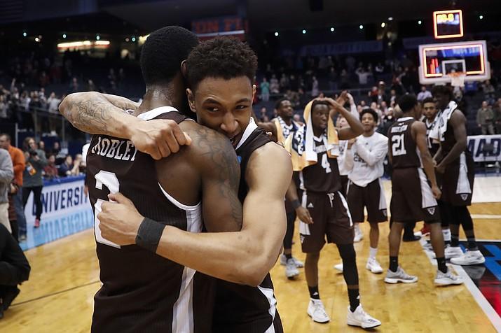 St. Bonaventure's Jaylen Adams, center, hugs Matt Mobley (2) after their First Four game of the NCAA men's college basketball tournament against UCLA on Tuesday, March 13, 2018, in Dayton, Ohio. St. Bonaventure won 65-58. (John Minchillo/AP)