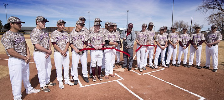 Winlslow Mayor Robin Boyd cuts the ribbon rededicating Vargas Baseball Field in Winslow while the Winslow High School baseball team looks on. Photo/Todd Roth