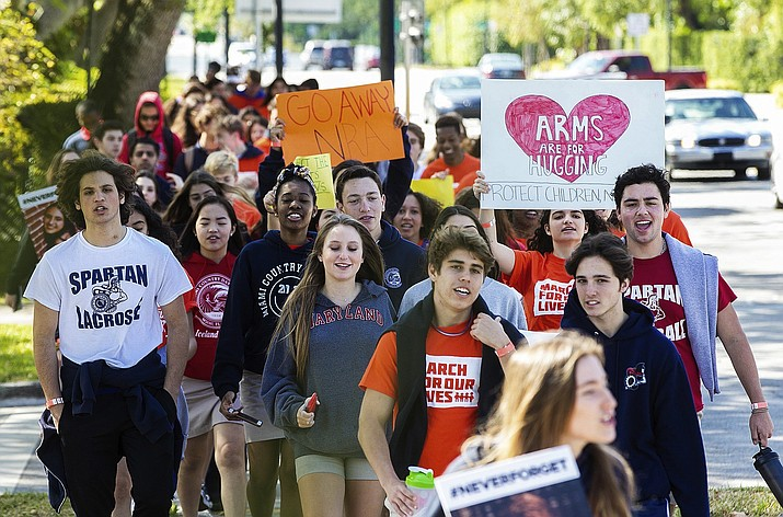 CORRECTS MONTH TO MARCH Hundreds of students from Miami Country Day, a private school in Miami Shores, Fla., take to the streets in the national students walkout protesting gun violence and honoring the 17 students and teachers that were killed last month at Marjory Stone Douglas High School on Wednesday, March. 14, 2018, in Parkland. (C.M. Guerrero/Miami Herald via AP)