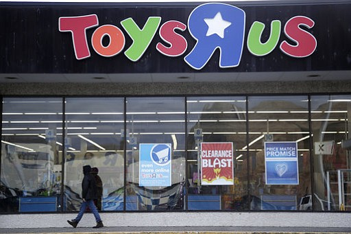 This Jan. 24, 2018, file photo shows a person walking near the entrance to a Toys R Us store, in Wayne, N.J. Toys R Us CEO David Brandon told employees Wednesday, March 14, 2018, that the company's plan is to liquidate all of its U.S. stores, according to an audio recording of the meeting obtained by The Associated Press. (AP Photo/Julio Cortez, File)