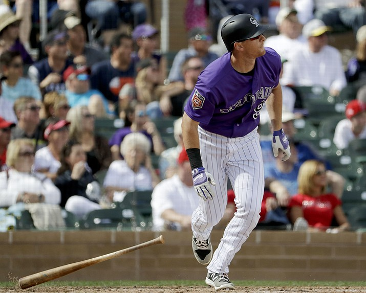 Colorado Rockies' DJ LeMahieu watches his grand slam against the Los Angeles Angels during the fourth inning of a spring baseball game in Scottsdale, Ariz., Thursday, March 15, 2018.